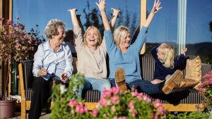 Neljä naista kolmessa polvessa istuu parvekkeen sohvalla. Keksimmäiset naiset ovat nostaneet jalat ja kädet ylös riemuiten.