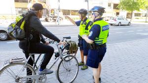 Cyklist på trottoaren stoppas av två poliser.