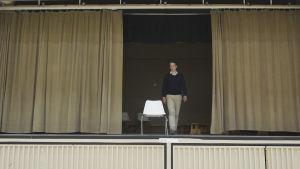 En man går på en scen. Draperierna är halft fördragna och på scenen står en vit stol. Mannen går mot stolen.