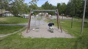 En man sitter i en gunga på en skolgård. I bakgrunden syns en lekplats.