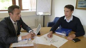 Två män sitter vid ett bord. De samtalar och tittar på planritningar över ett hamnområde.
