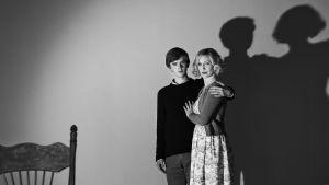 Äiti ja poika seisovat tyhjähkössä huoneessa, mustavalkoisessa kuvassa.