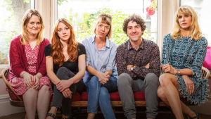 neljä naista ja mies istuvat sohvalla ja katsovat kameraan.