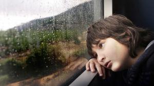 Lapsi katsoo sateisella säällä ikkunasta ulos.