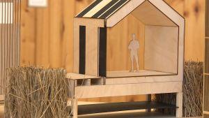 Ett miniatyrhus av trä där en figur står i byggnaden, ett exempel på hur hus i skärgården kunde se ut