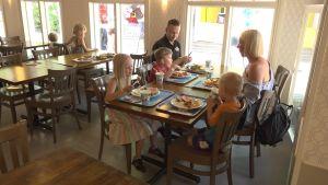 En familj med mamma, pappa och tre barn sitter vid ett restaurangbord.
