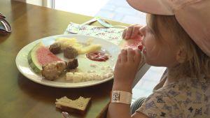 En liten flicka med ljusröd keps äter vattenmelon. Framför sig har hon en talrik med köttbullar, en kycklingklubba och potatismos.