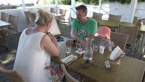 Familjen Linda Massalin, Vesa Ovaska och Fanny Massalin studerar en meny på en restaurang.