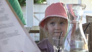 Fanny Massalin sitter vid ett restaurangbord med en röd mössa med spets och vita prickar.
