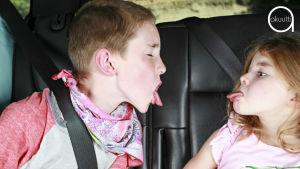 Kaksi lasta autonpenkillä, toinen näyttää kieltä.