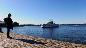 Nainen seisoo Suomenlinnan lauttarannassa ja katsoo merelle.