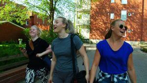 Kolme naista kävelee iloisena kadulla kesällä.