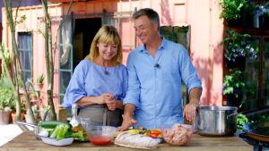 Nainen ja mies valmistamassa ruokaa puutarhan terassilla.