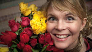 Runoilija Heli Laaksonen ruusujen keskellä