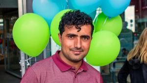 Nuori mies ilmapallojen edessä, kasvokuva.