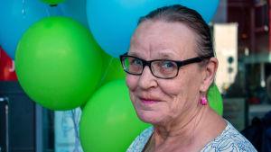 Keski-ikäinen nainen ilmapallojen edessä, kasvokuva.
