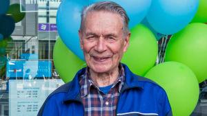 Eläkeikäinen mies ilmapallojen edessä, kasvokuva.
