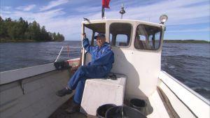 äldre man sitter i båt
