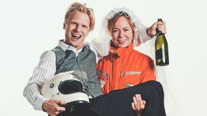 Joppe Dikert iklädd formulaoverall med sin man Oskar Pöysti i famnen. Han har en formel1- hjälm i famnen och en champagneflaska i handen. De ser ivriga och glada ut.