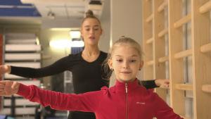 Rytmiska gymnasterna Rebecca Gergalo och Lia Kallio gör balettövningar vid ribbstol.