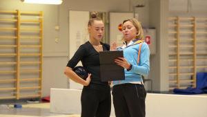 Rytmiska gymnasten Rebecca Gergalo och tränaren Larisa Gryadunova diskuterar.