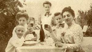 Poika, nainen ja kolme nuorempaa naista tai tyttöä istuvat ruokapöydän ääressä ja nostavat maljoja. 1890-1909