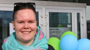 Nainen Oulun kirjaston edessä.