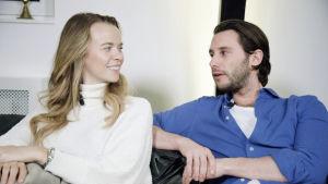 nainen ja mies istuvat sohvalla ja katsovat toisiinsa.