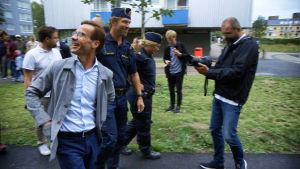 Moderaternas partiledare vandrar bredvid poliser och blir filmad. Hanär klädd i grå kavaj och vit skjorta och tittar leende snett bakåt och uppåt.
