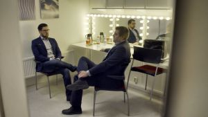 Jimmie Åkesson sitter i en loge och väntar tillsammans med en annan man. Båda är klädda i mörk kostym och ser fundersamma ut. De sitter med ena benet upp på det andra.