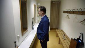 Ulf Kristersson, klädd i mörkblå kostym, är fotograferad i profil där han står i ett omklädningsrum och tittar in i en spegel.