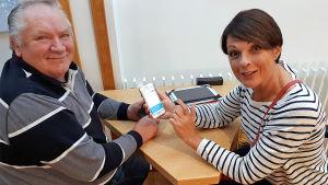 Anna-Liisa Tilus opastaa seniorille kännykän käyttöä Rovaniemen kirjastossa.