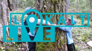 Två pojkar kramar ett tjockt träd genom att hålla varandra i händerna. Med turkosa lokalt live-logon på.