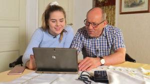 Nuori nainen auttaa isoisäänsä tietokoneen käytössä.