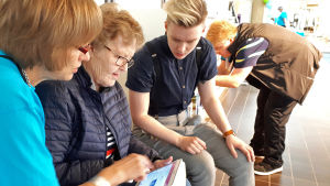 Kaksi digiauttajaa neuvoo eläkeikäistä naista Rovaniemen pääkirjastolla.