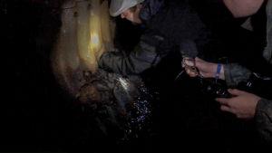 Ett mörkt rör, vatten flödar genom röret. Henrik Kettunen och Lukas Rusk står i röret, Kettunen sätter in sin hand i en spricka i rörets vägg.