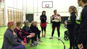 En grupp kvinnor i ring informeras om modern femkamp.