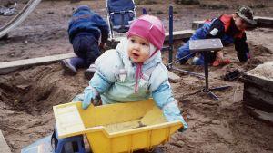 Lapsia leikkimässä hiekkalaatikolla.