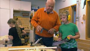 Äldre person tillsammans med en pojke med hörlurar på och såg i handen.