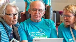 Enter ry:n opastajia ja asiakas katsovat tietokonetta Nettiä ikä kaikki -kiertueella Espoossa Sellon kirjastossa.