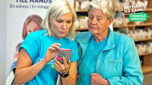 Sanna Savikko neuvoo kännykän käytössä rouvaa Nettiä ikä kaikki -kiertueella Turussa.