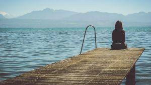 Nainen laiturilla katselee merta.