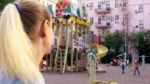 Sijaissynnyttäjä Elena Venäjältä katselee lapsia leikkipuistossa