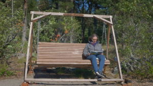 Eva Hietanen läser i en trädgårdsgunga