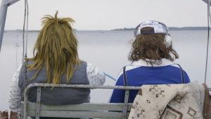 Anton och Johannes utklädda bakifrån ser ut över havet