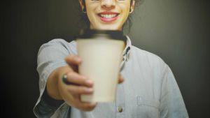 Nainen ojentaa kahvikuppia.