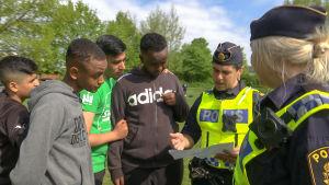 Kaksi poliisia keskustelee ringissä nuorten miesten kanssa.