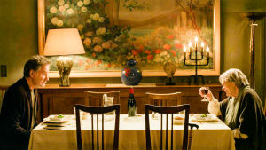Kevin kline ja Maggie Smith istuvat pöydän molemmissa päissä ja Smith nostaa maljaa.