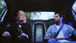 Kaksi miestä istuu auton takapenkillä. Toisella on epämääräisesti muotoutuneet kasvot.