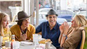 Kaksi miestä ja kaksi naista istuu kahvilapöydän äärellä ja nauraa